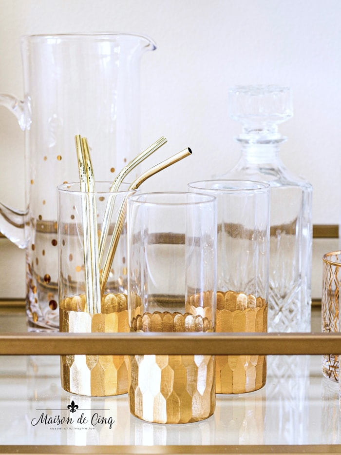 bar cart holding gold rimmed cocktail glasses and crystal liquor bottles
