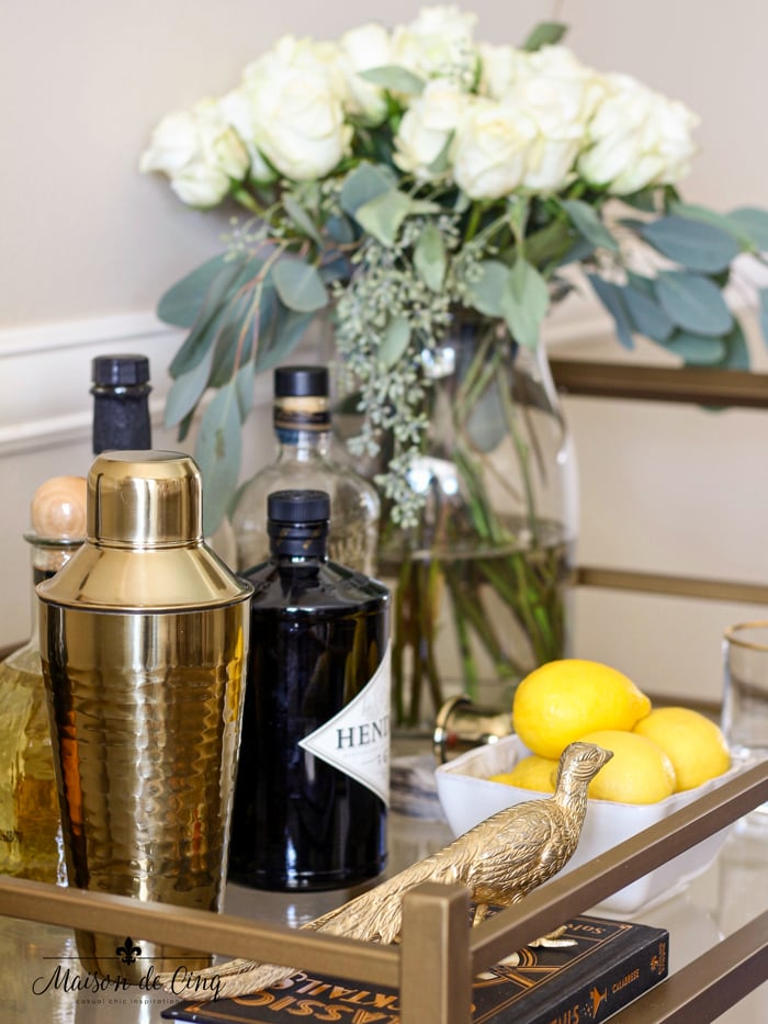 bar cart styling with cocktail shaker liquor bottles lemons and accessories