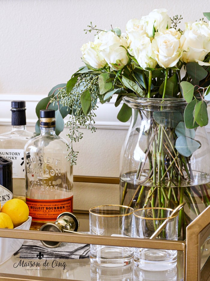 bar cart styling with roses and gold rimmed glasses