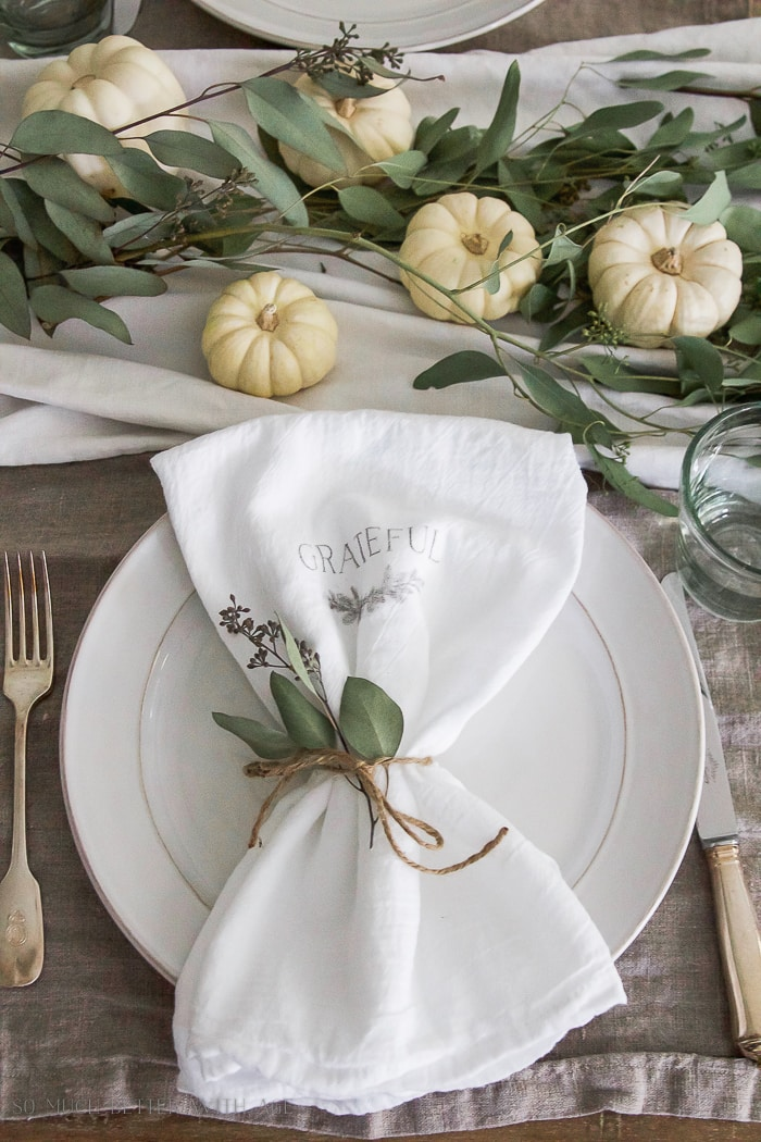 neutral Thanksgiving table with white pumpkins and eucalyptus