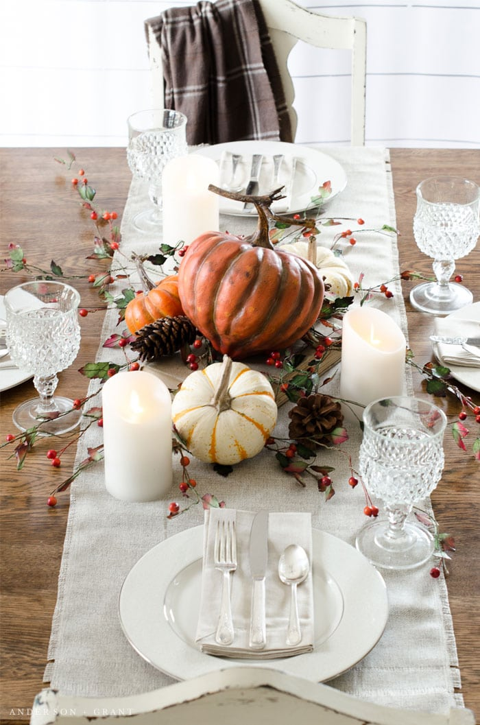 traditional Thanksgiving tablescape with pumpkins candles and berries