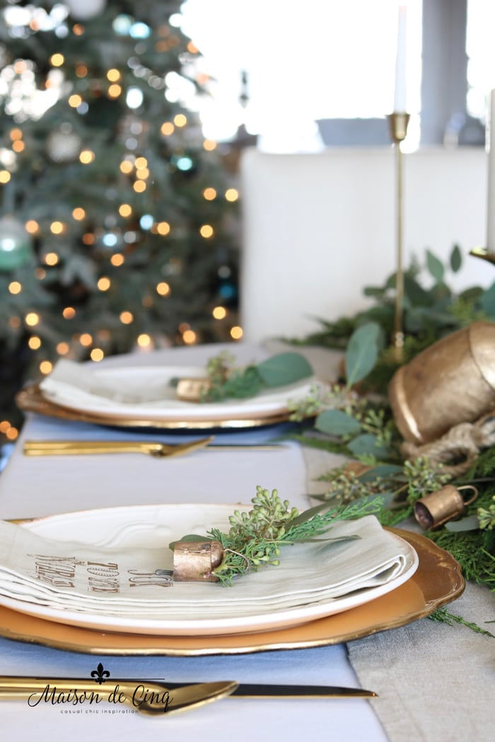 gorgeous holiday tablescape with Pottery Barn napkins and greenery Christmas tree lights