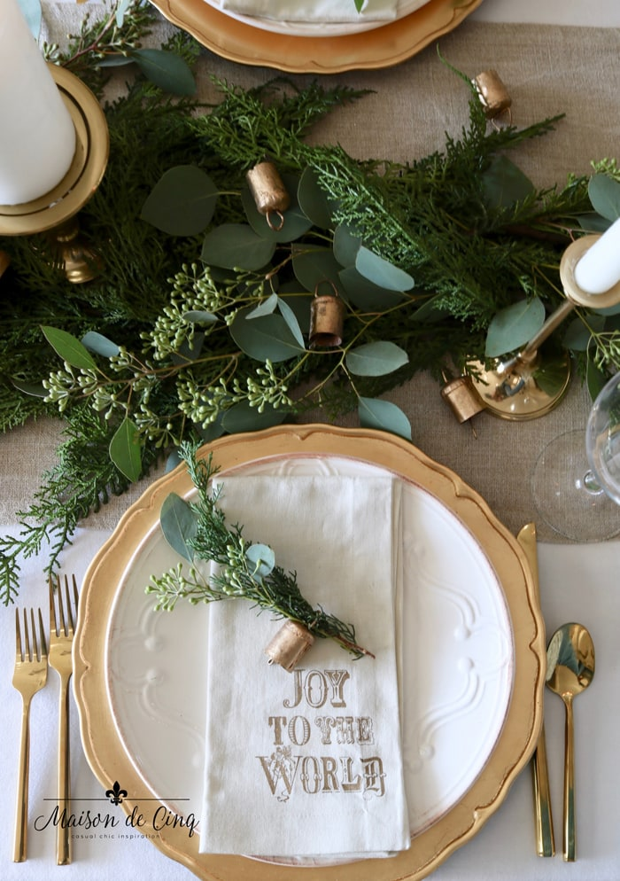 gorgeous holiday table setting with greens, eucalyptus and gold chargers