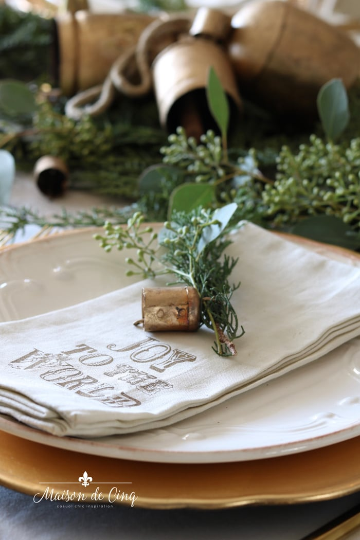 cute Pottery Barn graphic Christmas napkin with sprigs of pine and eucalyptus and a brass bell