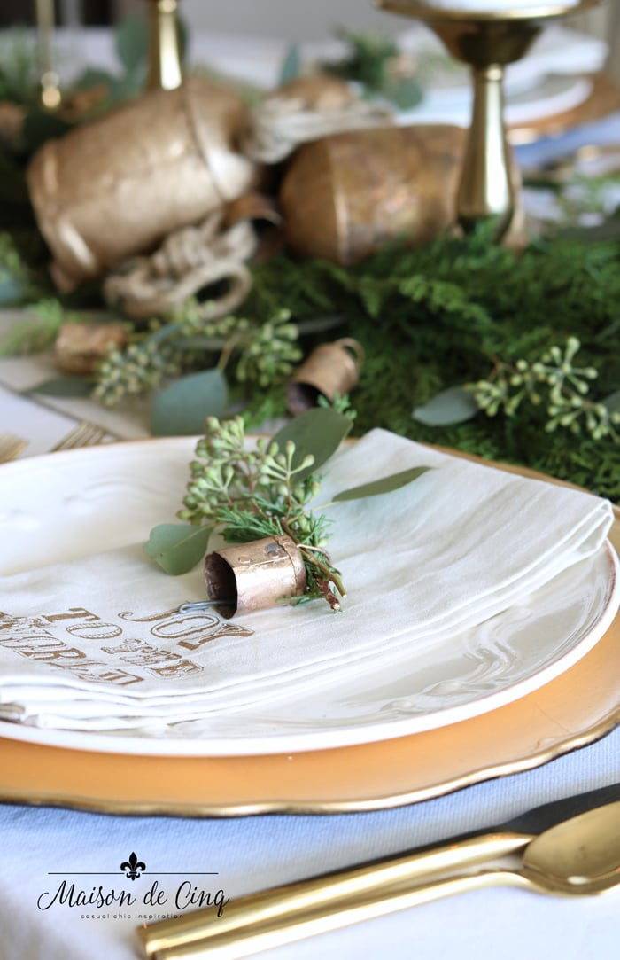 Pottery Barn napkin, brass bells, and sprigs of pine and eucalyptus place setting holiday table