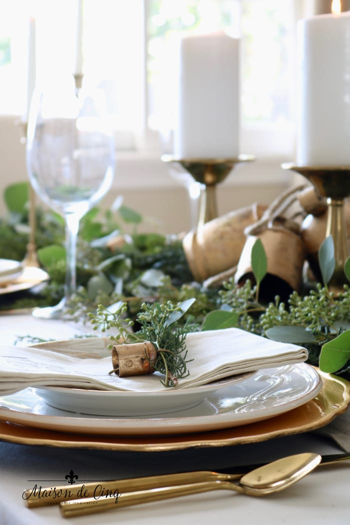 holiday table with white plates, gold chargers and greens