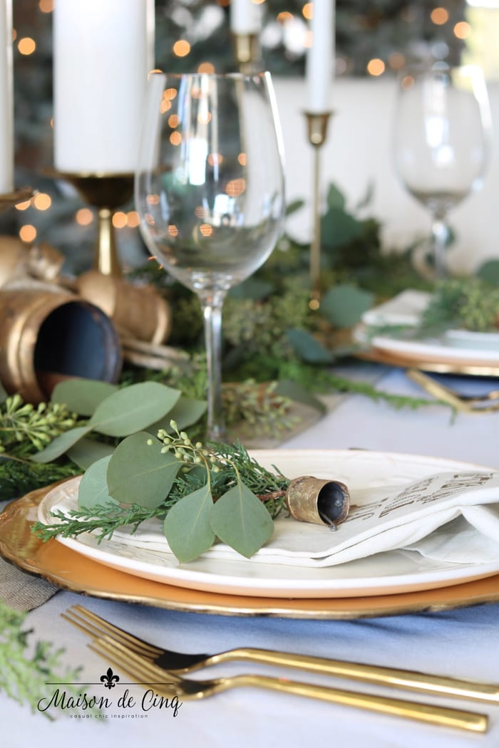 pretty Christmas table with gold chargers, gold flatware, and brass bells