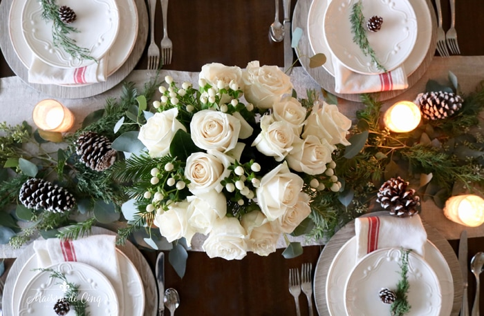 overhead view of classic red Christmas table setting with roses pinecones and greens