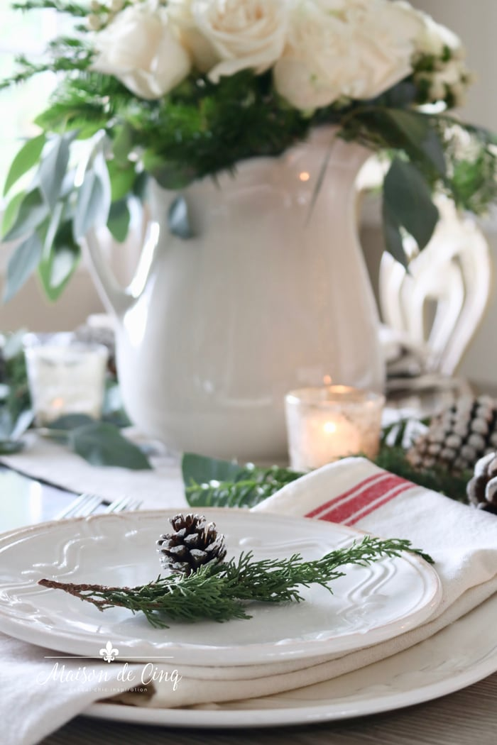 white plates, red striped napkins, white roses on classic Christmas table setting