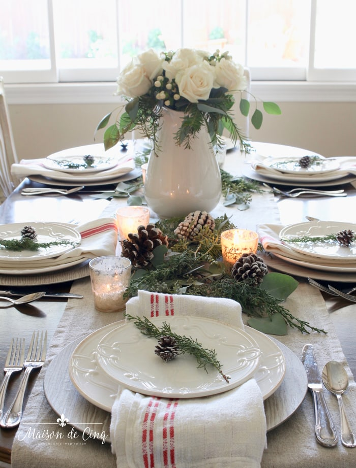 stunning classic Christmas table setting with roses and pinecones