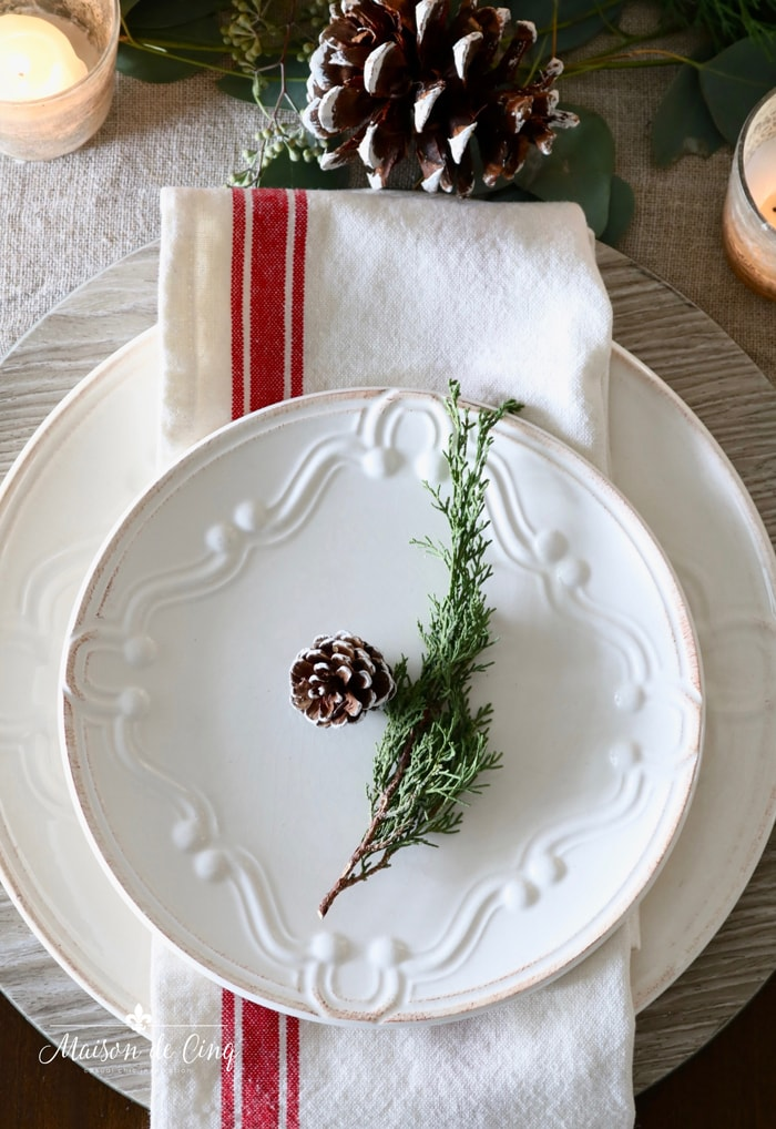white plates with wood charger pinecones and greens