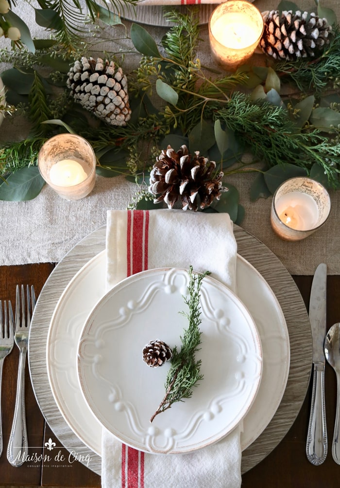 white plates with red striped napkin pinecones votives and greens