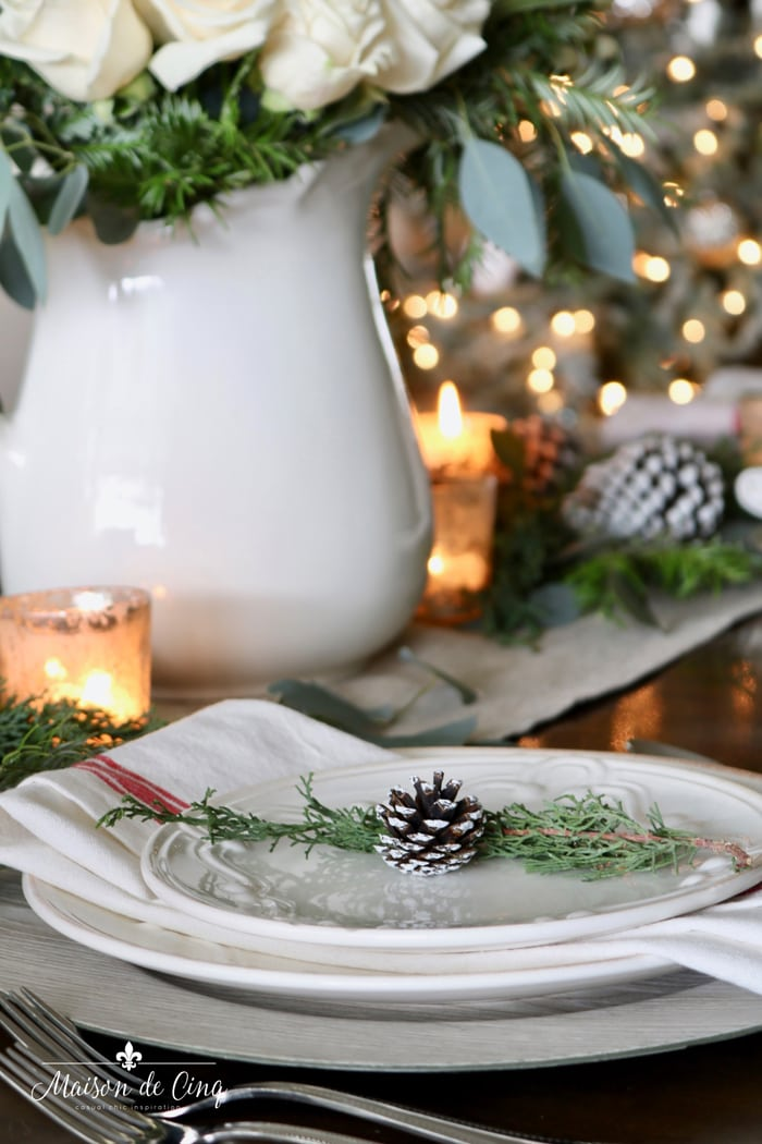 close up of pinecone on plate on Christmas table with white roses