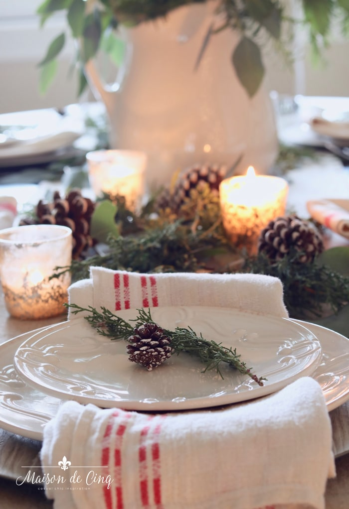 beautiful close up of pinecone and greens on plate in classic christmas table setting