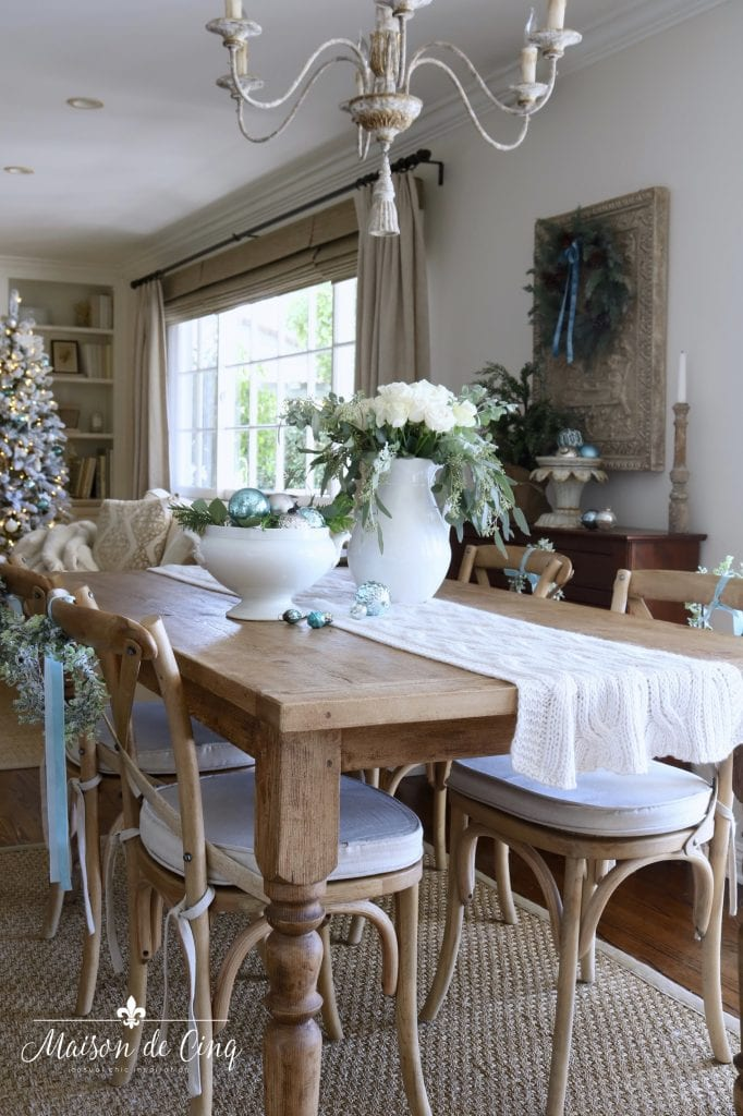 farmhouse dining table Christmas decor with white roses and blue ornaments and ribbon