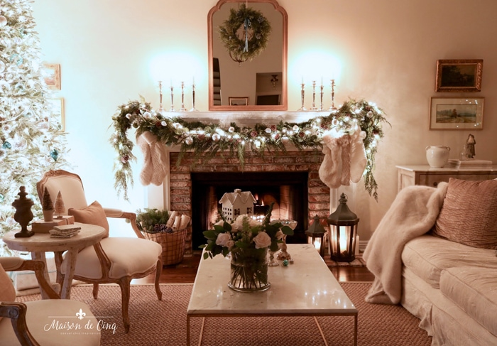 french country living room mantel with garland stockings wreath on mirror