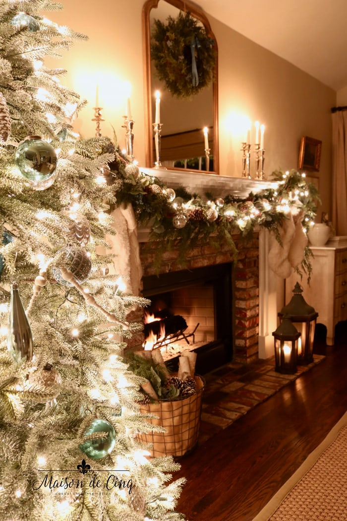 christmas mantel with lit garland and candles