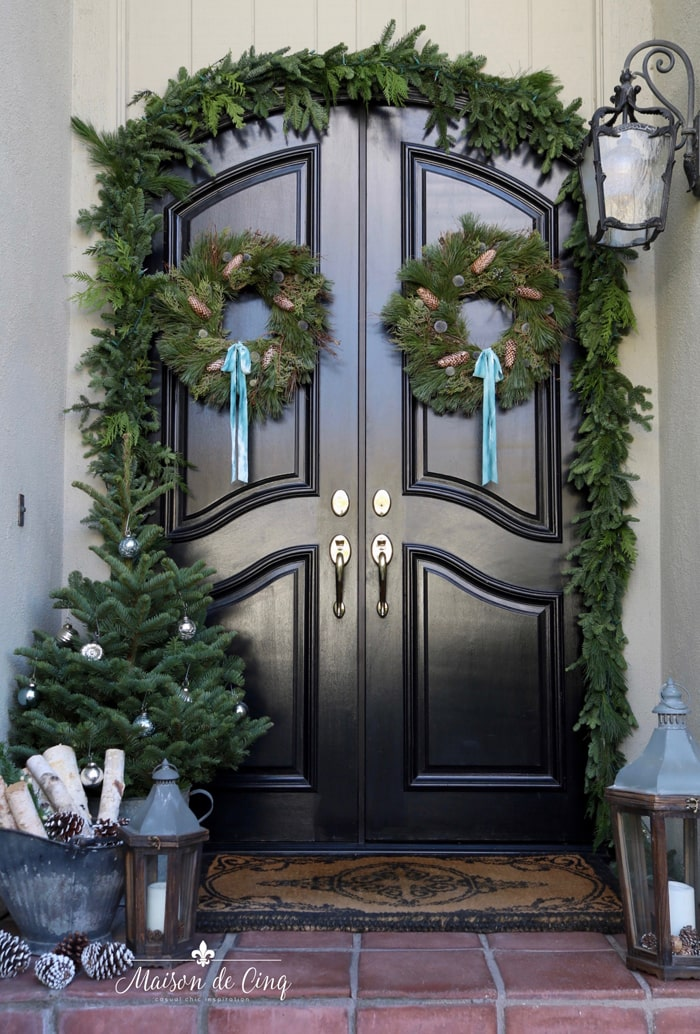gorgeous holiday porch decorated with wreaths and garland and lanterns classic Christmas decor