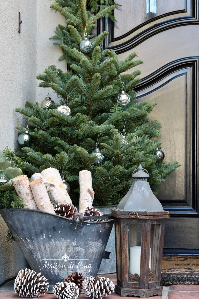 holiday porch decorating ideas small noble fir bucket with pinecones and lantern