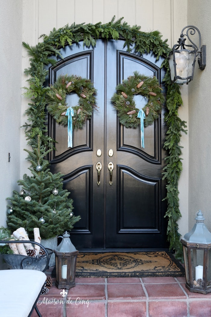 black front doors Christmas porch decorated with greens
