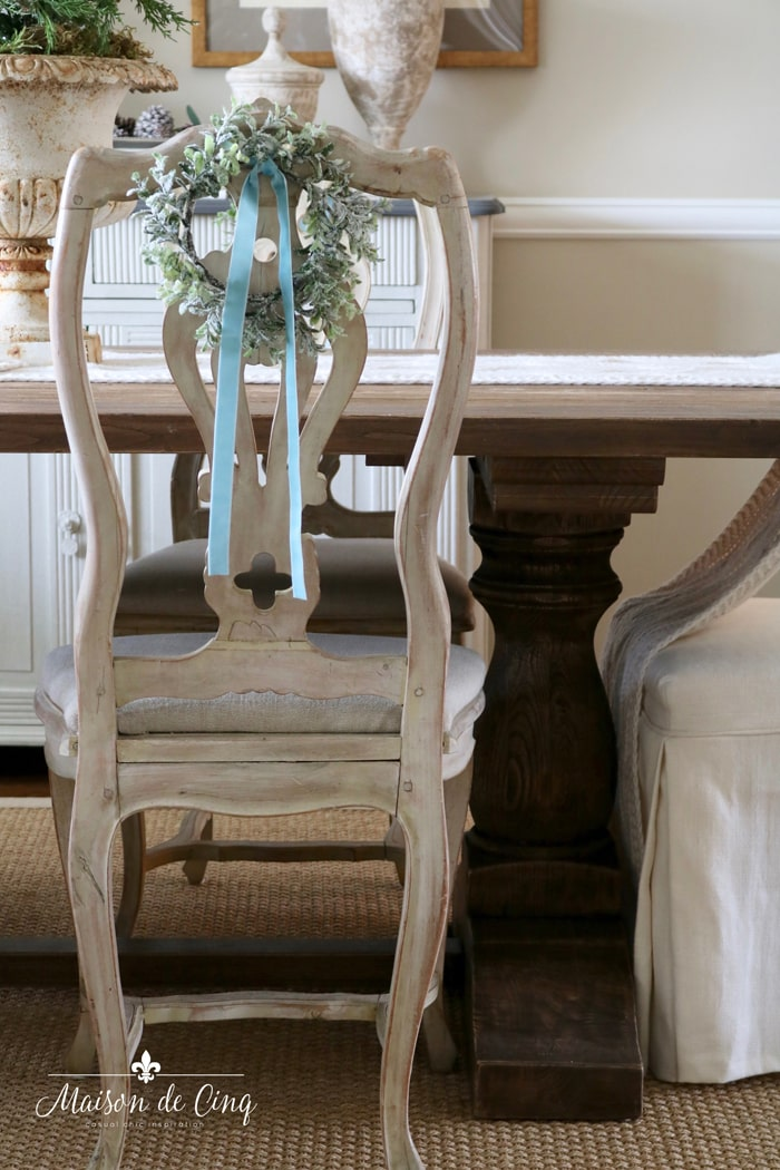 Christmas wreath on chair in gorgeous French country dining room holiday decor