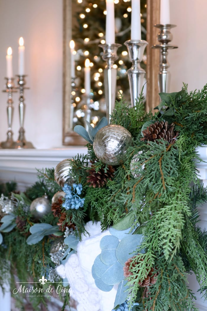 mercury glass ornaments and pine cones in cedar garland on mantel French country Christmas