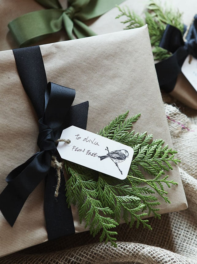 pretty holiday gifts with craft paper and black ribbon and greens