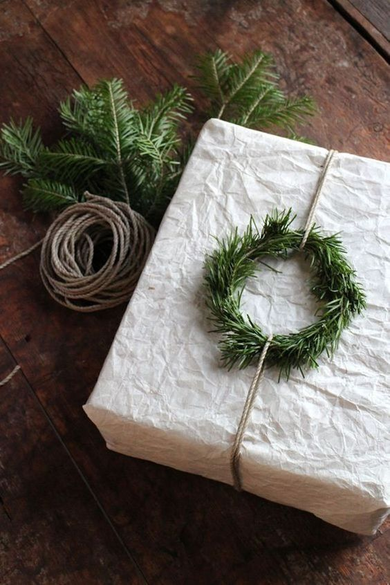 white wrapping paper with rosemary wreath holiday gift