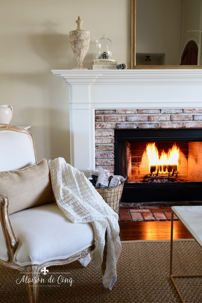 fireplace with cozy fire burning mantel mirror french chair