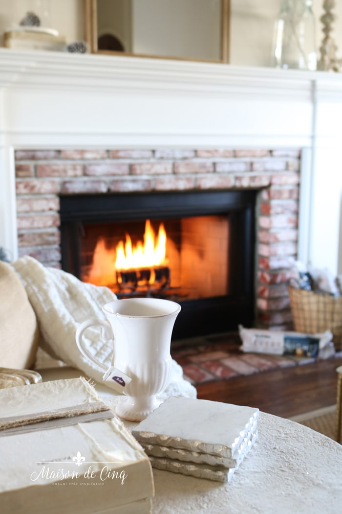 tea and cozy blanket by fireplace in French country living room