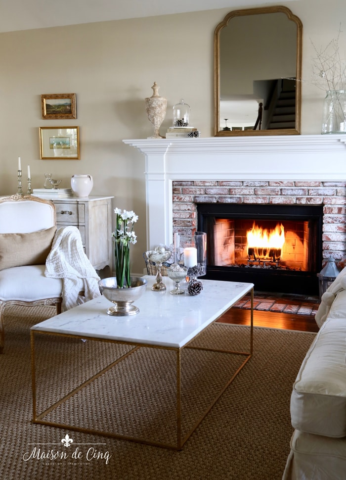 gorgeous French country living room with fire in fireplace mirror over mantel
