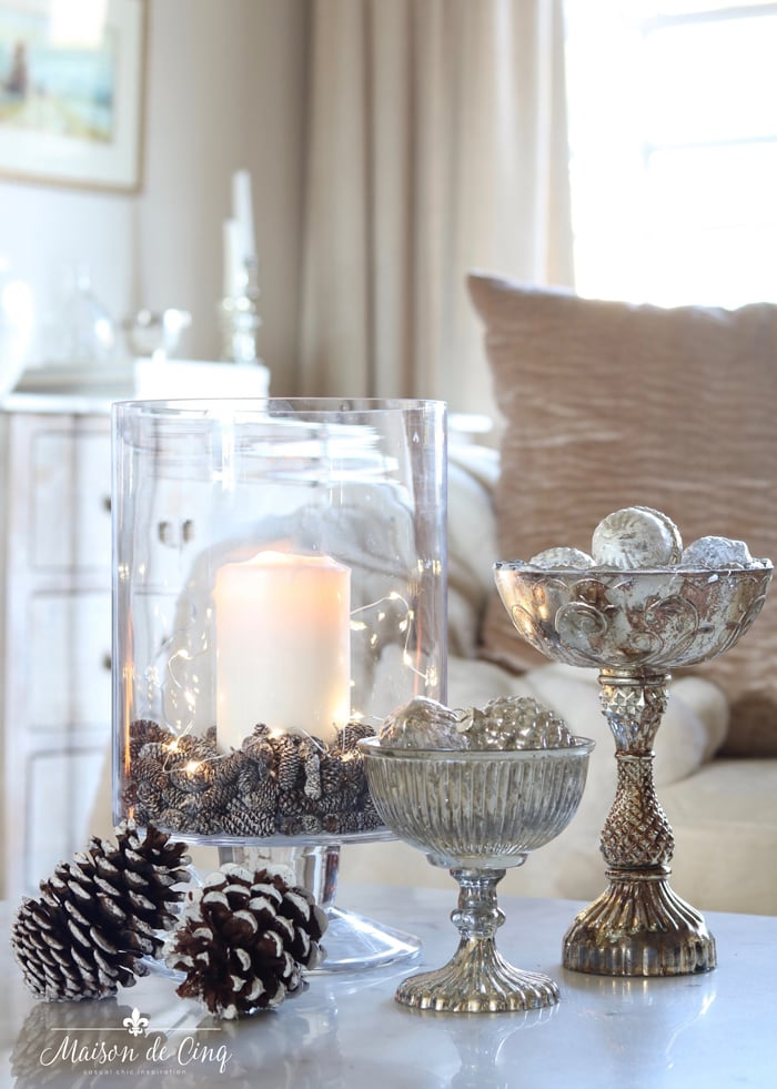 winter decor ideas lights in vase pine cones and silver ornaments