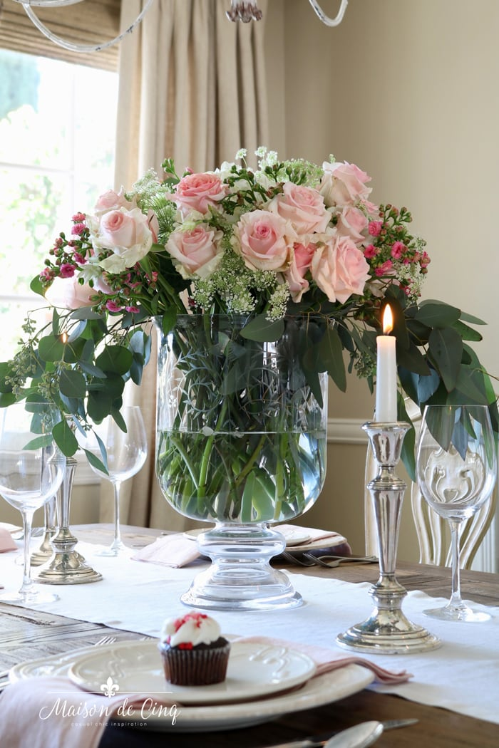 Valentine's day table setting with gorgeous pink roses in glass vase silver candleholders