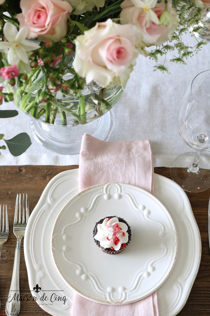 white plates with pink napkin and pink roses Valentine's day table setting