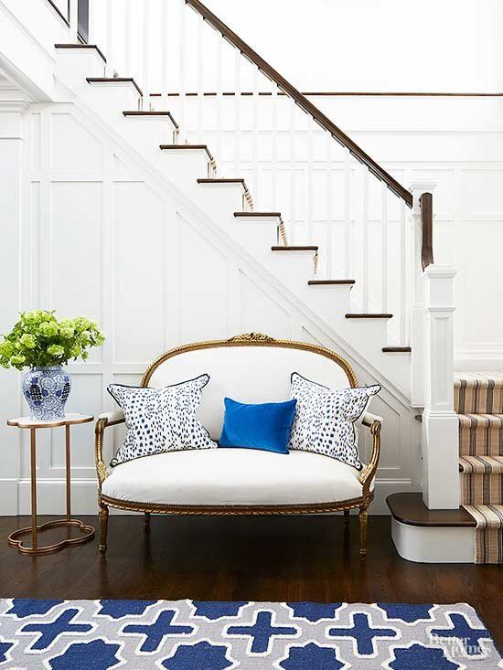 white entry way with pops of blue pillow french settee staircase