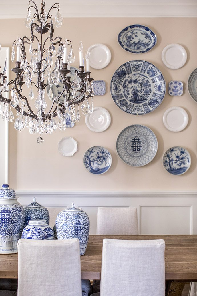 dining room with blue and white ginger jars and plates on wall crystal chandelier