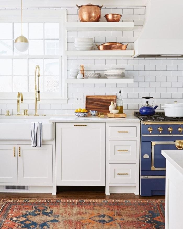 white kitchen with blue French range stove subway tile copper pots