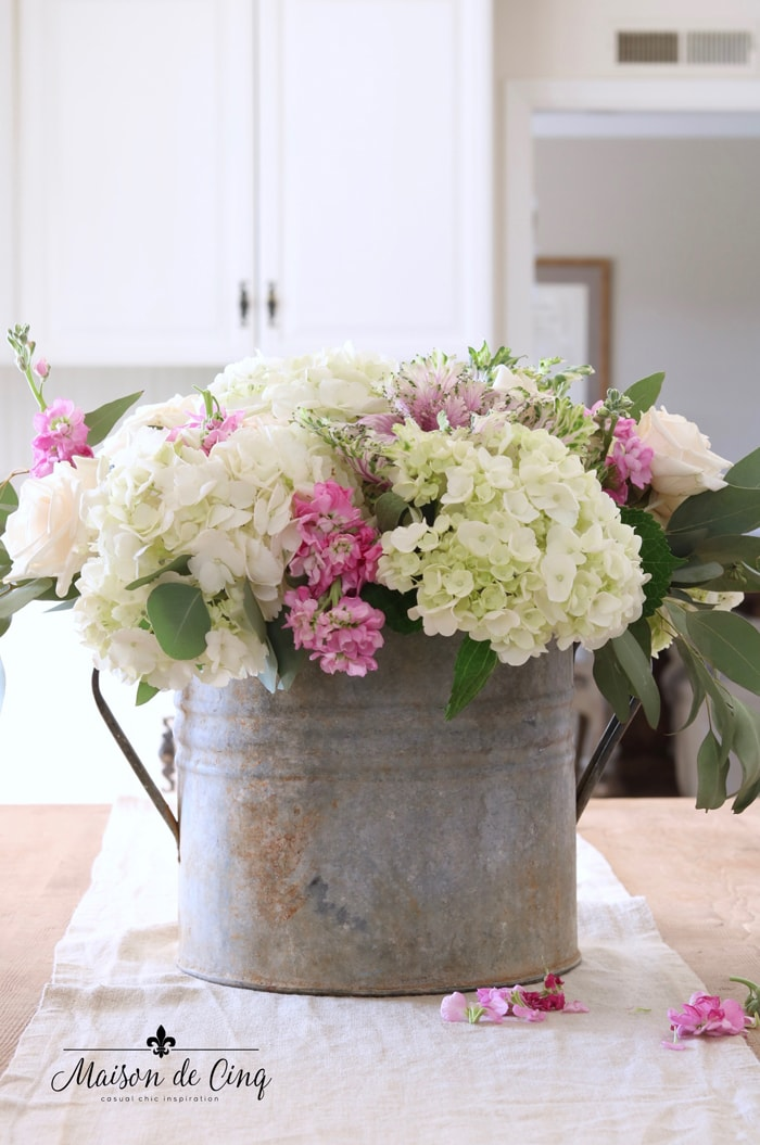 rustic French vintage bucket with hydrangeas pink stock and ornamental kale gorgeous spring flowers