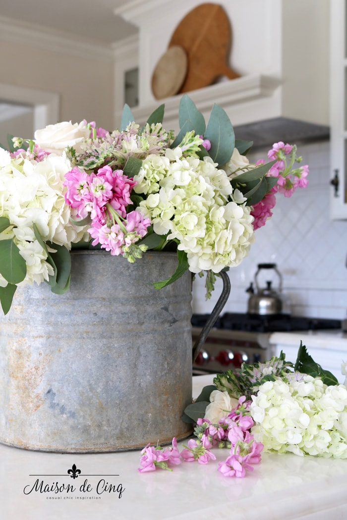 gorgeous arrangement of spring flowers in vintage bucket in white farmhouse kitchen