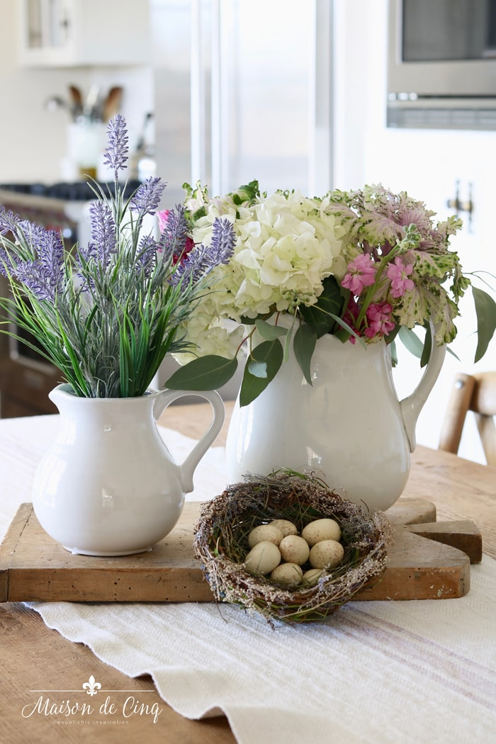 spring vignette on kitchen table ironstone pitchers with flowers nest with eggs on bread board