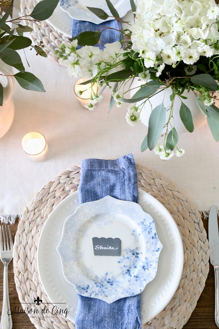 beautiful spring table setting tablescape idea with floral plates blue napins seagrass charger and white flowers