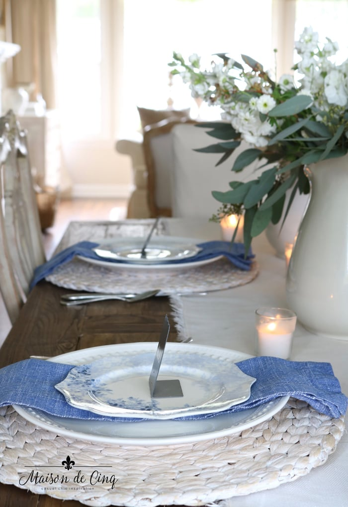 blue napkin and blue floral plates on seagrass charger pretty spring table