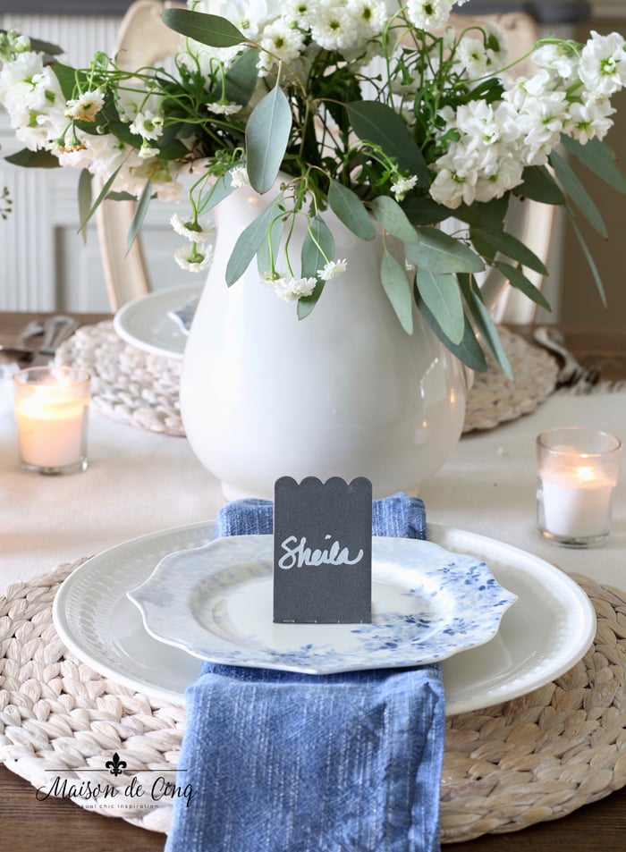 gorgeous spring table setting idea with chalkboard place cards blue napkins floral plates and white flowers