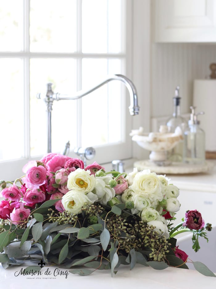 gorgeous ranunculus in sink in white farmhouse kitchen