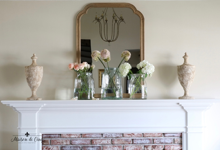pretty spring mantel with florals in glass vases