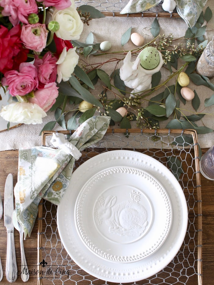 Easter table setting with ranunculus easter eggs bunny plates and chicken wire chargers