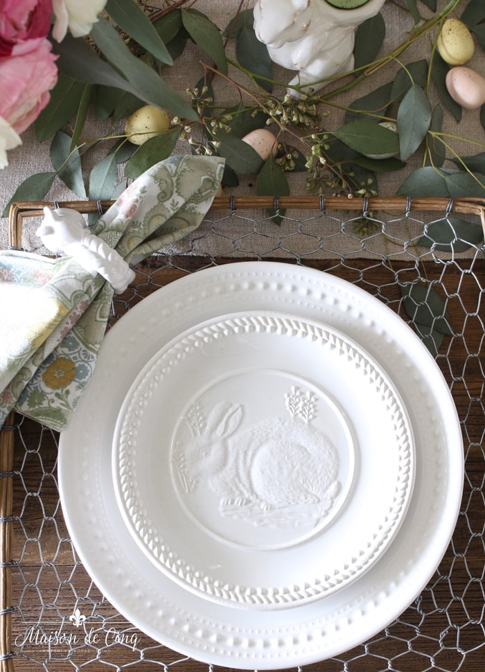embossed white bunny plates on chicken wire chargers paisley napkin flowers easter eggs scattered