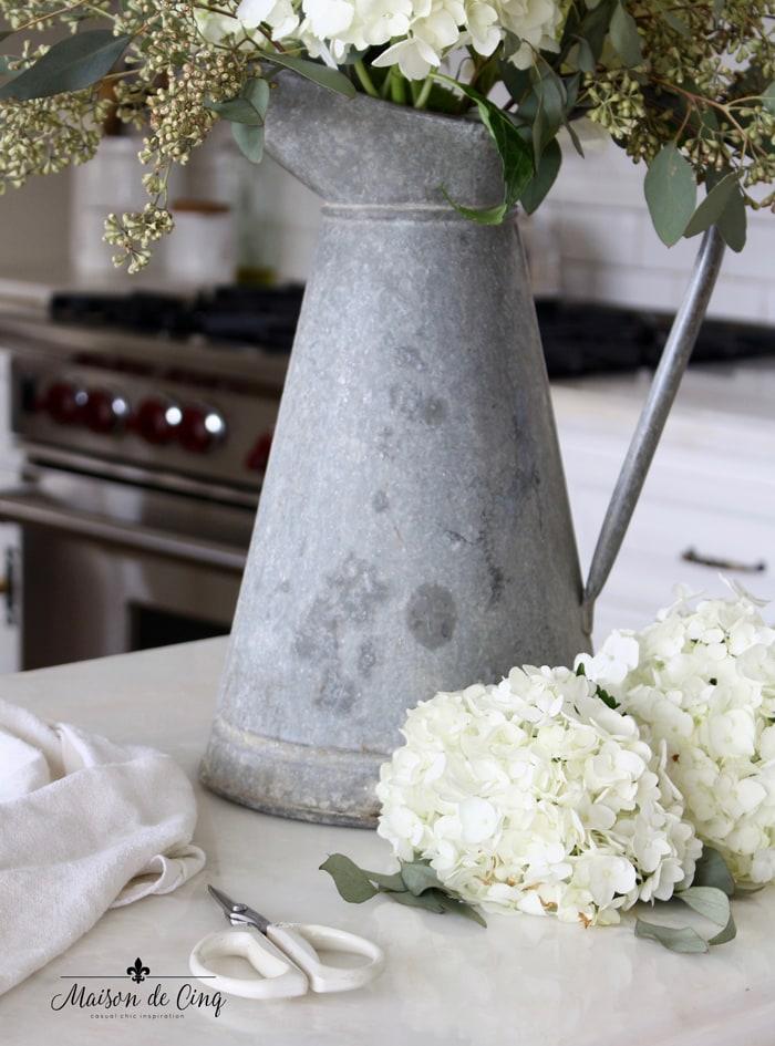 French zinc galvanized pitcher with white hydrangeas in kitchen
