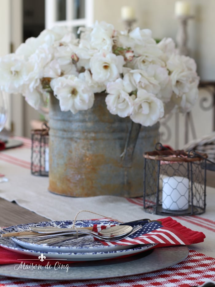 galvanized bucket of flowers on patriotic table setting summer decor