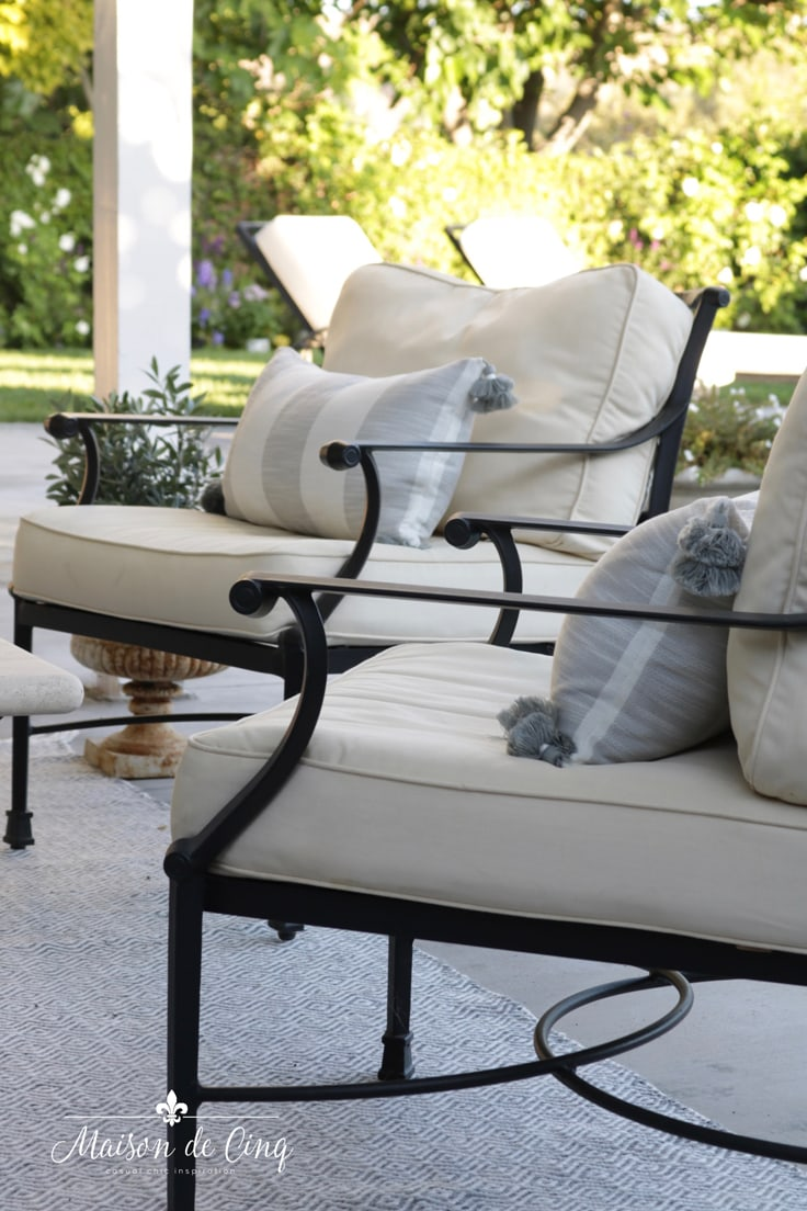outdoor patio refresh with black iron chairs and grey and white striped pillows